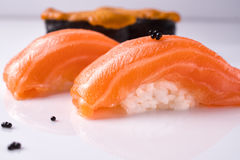 Two pieces of Japanese salmon nigiri sushi, piece of uni gunkan on a white reflective surface decorated black tobiko. Close up. Two pieces of Japanese salmon stock photo