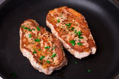 Two pieces of meat on a frying pan Royalty Free Stock Photography