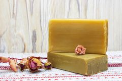 Two pieces of the natural handmade organic olive oil soap and Dry rose flowers and buds on the wooden table. Bath spa accessories. Stock Images