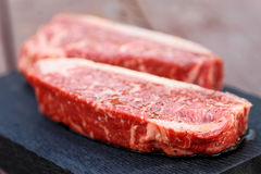 Two Pieces Of Raw Steak On Wooden Plank, Toned Stock Images