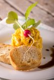 Two pieces of pastry in front of scrambled eggs. Vertical photo of single portion of yellow scrambled eggs. Eggs in shape of tower. Single small red raw radish Royalty Free Stock Image