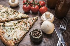 Two pieces of pizza, beer, champignons, cherry tomatoes on a branch, fork and knife royalty free stock photo