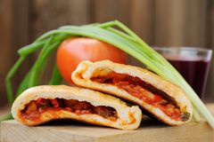 Two pieces of pizza calzone with glass of red wine, fresh scalli Royalty Free Stock Image