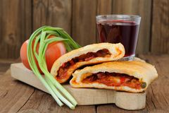 Two pieces of pizza calzone with glass of red wine, fresh scalli Royalty Free Stock Photo