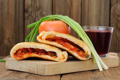 Two pieces of pizza calzone with glass of red wine, fresh scalli Royalty Free Stock Images