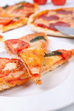 Two pieces of pizza closeup. Two pieces of pizza margharita close-up on a white plate and more at the back Royalty Free Stock Photos