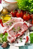 Two pieces of pork on a cutting board and fresh foods, vertical Royalty Free Stock Photo