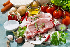 Two pieces of pork on a cutting board and fresh ingredients Royalty Free Stock Image