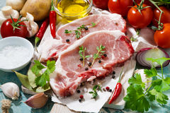 Two pieces of pork on a cutting board and fresh ingredients Stock Photo
