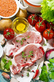 Two pieces of pork on a cutting board and fresh ingredients Stock Images