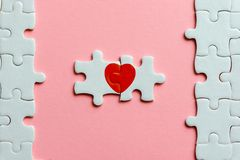 Two pieces of a puzzle with red heart on pink background stock photos