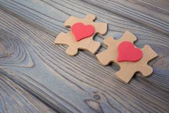 Two pieces of a puzzle with a red heart, unite into a single whole. Holiday, St. Valentine`s Day. Lovers` day, close-up Stock Image