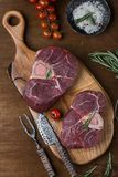 Two pieces of raw meat for ossobuco. On a wooden chopping board Stock Photos