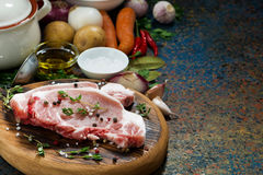 Two pieces of raw pork on cutting board and ingredients. Horizontal Stock Photos
