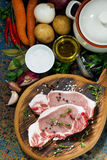 Two pieces of raw pork on cutting board and ingredients. Vertical, top view, closeup Royalty Free Stock Photography