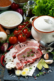 Two pieces of raw pork and fresh ingredients for soup, vertical. Two pieces of raw pork and fresh ingredients for soup,  top view Stock Image