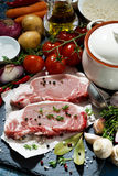 Two pieces of raw pork and ingredients for preparation of soup Royalty Free Stock Photos