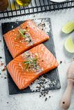 Two pieces of raw salmon fillet with fresh herb rosemary, spices and olive oil on black slate plate.  Royalty Free Stock Photo