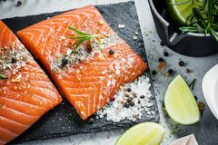 Two pieces of raw salmon fillet with fresh herb rosemary, spices and olive oil on black slate plate Stock Photo