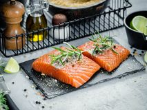 Two pieces of raw salmon fillet with fresh herb rosemary, spices and olive oil on black slate plate Royalty Free Stock Photography
