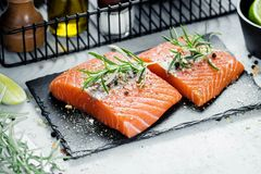 Two pieces of raw salmon fillet with fresh herb rosemary, spices and olive oil on black slate plate Royalty Free Stock Image