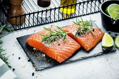 Two pieces of raw salmon fillet with fresh herb rosemary, spices and olive oil on black slate plate.  Stock Images