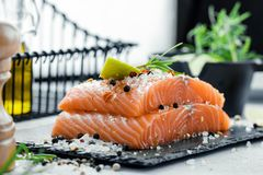 Two pieces of raw salmon fillet with fresh herb rosemary, spices and olive oil on black slate plate.  Royalty Free Stock Photography