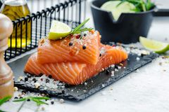 Two pieces of raw salmon fillet with fresh herb rosemary, spices and olive oil on black slate plate Royalty Free Stock Images