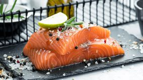 Two pieces of raw salmon fillet with fresh herb rosemary, spices and olive oil on black slate plate.  Stock Photos