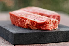 Two pieces of raw steak on wooden plank, toned. Two pieces of raw striploin steak, outdoor shot, toned Royalty Free Stock Images
