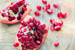 Two pieces of red pomegranate on the wooden background Royalty Free Stock Images