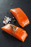 Two pieces Salmon with herbs on black background. Royalty Free Stock Images