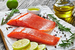 Two pieces of salted salmon fish fillet. With fresh rosemary, mix of pepper, oil in gravy boat on chopping board on paper, close-up Royalty Free Stock Images