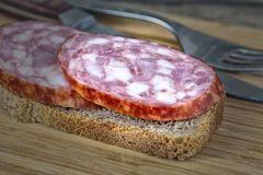 A piece of sausage on bread royalty free stock photos