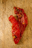 Two pieces of sun-dried tomatoes  on old wood Royalty Free Stock Photo