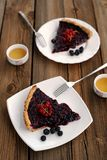 Two pieces of tart with black currant and blackberry filling and green tea. On wooden background Stock Photo