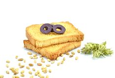 Two pieces of toast bread with olives and grains of wheal on white background royalty free stock photos