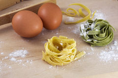 Two pieces of yellow and green pasta with two brown eggs on table Royalty Free Stock Photos