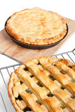 Two pies. Closed pie on a wooden board and open on a metal railing Stock Images