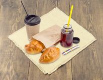 Two pies and tea in paper cup and plastic container Royalty Free Stock Image