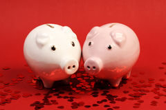 Two piggies bank in love standing on red background with red shining heart glitters Royalty Free Stock Image