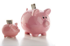 Two piggy banks. Close-up of two piggy banks, one little one and one large one, isolated on white Royalty Free Stock Photography