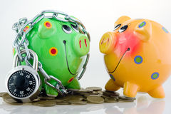 Two piggy banks. A yellow piggy bank and a locked green piggy bank with coins Stock Images