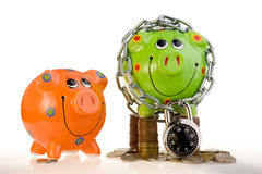 Two piggy banks. Two different piggy banks, the green one secure with a locked chain on stacked coins and the orange one insecure Royalty Free Stock Photography