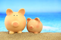 Two piggy banks. On the beach Stock Image