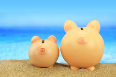 Two piggy banks on the beach. Looking to the sea Royalty Free Stock Photo