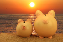 Two piggy banks on the beach. Looking to the sunset Stock Photography
