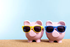 Two piggy banks, beach vacation savings, travel money concept, copy space. Two pink piggy banks on a beach with sunglasses.  Space for copy Stock Photos