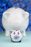 Two piggy banks on a blue blackground. Close up of a piggy bank on a blue blackground with blur Royalty Free Stock Image