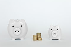 Two piggy banks coins unhappy. Two unhappy piggy banks, one small, one big, with a pile of coins, copyspace Stock Images
